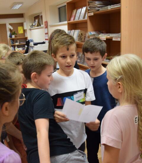 grupa dzieci stoi wokół chłopca czytającego z kartki
