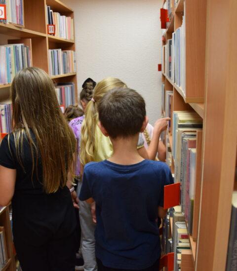 kilkoro dzieci stoi tyłem między regałami bibliotecznymi