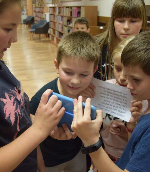 grupa dzieci odczytująca tekst w odbiciu lustrzanym