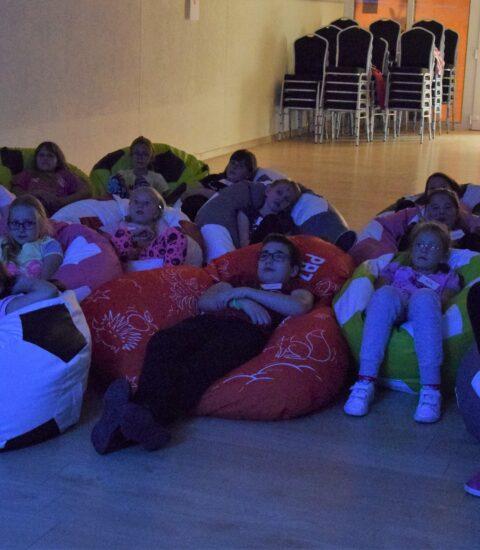 grupa dzieci siedzą na pufach, oglądają film