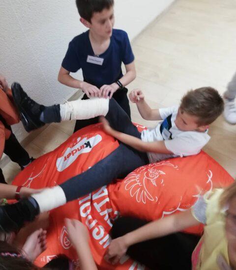 chłopiec leży na kolorowej pufie, drugi bandażem owija mu nogę