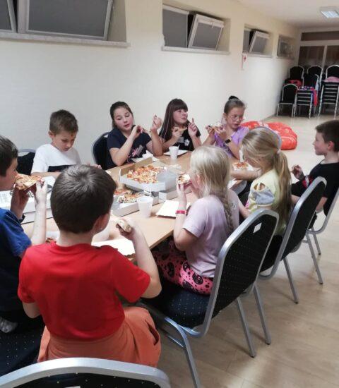 kilkoro dzieci siedzi przy stole, jedzą pizzę