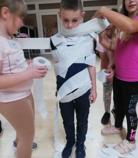 pośrodku chłopiec, którego trzy dziewczynki owijają papierem toaletowym