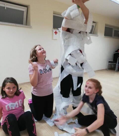 trzy dziewczynki na podłodze, obok postać owinięta papierem toalaetowym