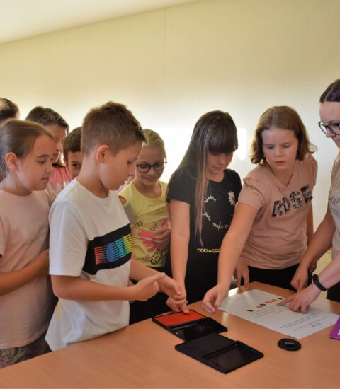 grupa dzieci składa odciski palców na kartce, przed nimi dorosła kobieta