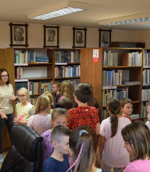 kobieta zwrócona w stronę grupy dzieci, wszyscy stoją między regałami bibliotecznymi